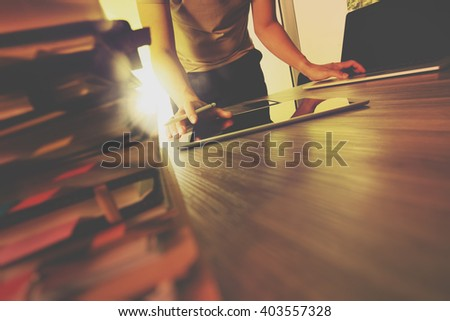 designer hand working with digital tablet and laptop computer and book stack on wooden desk as concept