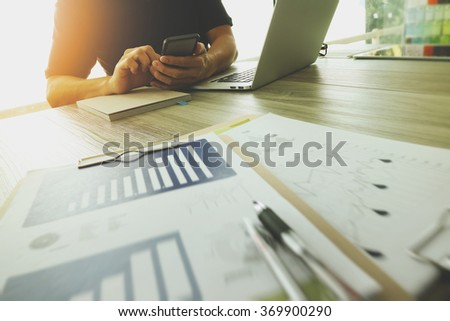 Designer hand working with laptop computer and smart phone and digital tablet on wooden desk as responsive web design concept - stock photo