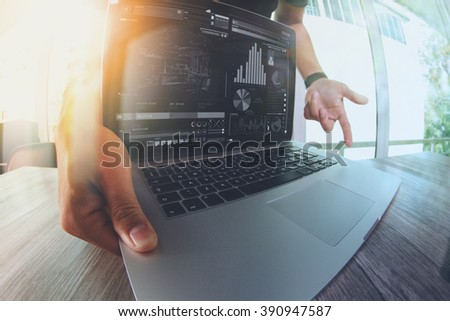 Designer hand working with laptop computer on wooden desk as responsive web design concept