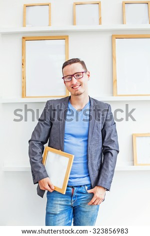 designer holding a blank picture. Many white papers in frames on background