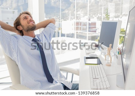 Designer leaning back at his desk in bright modern office - stock photo