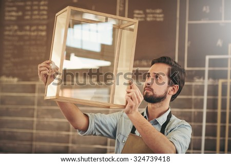 Designer looking carefully at a new product made from glass and wood in preparation for entrepreneurial marketing - stock photo