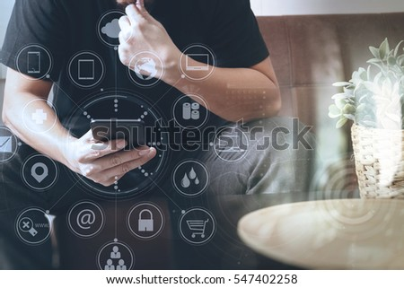 designer man hand using smart phone for mobile payments online shopping,omni channel,sitting on sofa in living room,vase rattan with plant and wooden tray on table,virtual icons graphics interface