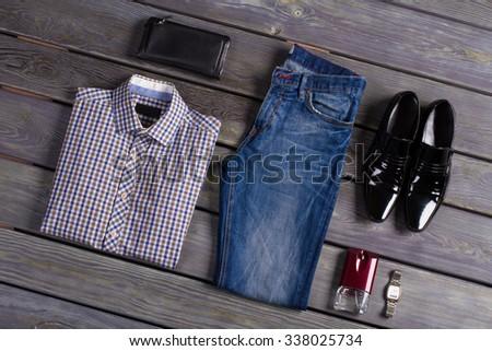Designer men's clothing on a dark wooden background. - stock photo