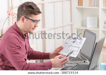 Designer or programmer working at new mobile applications - stock photo