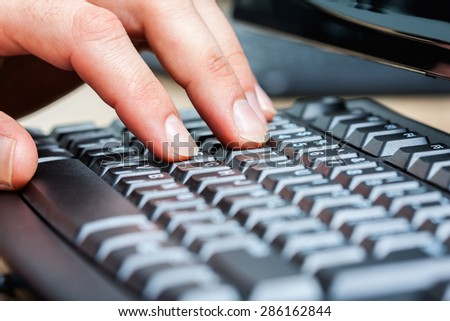 designer 's hand closeup. keyboard and monitor are blurred in the background. designer at work