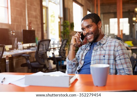Designer Sitting At Meeting Table Talking On Mobile Phone - stock photo