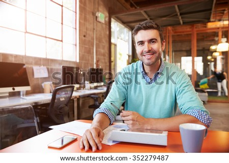 Designer Sitting At Meeting Table Working On Digital Tablet