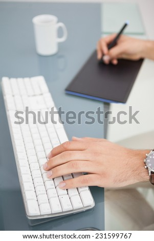 Designer using digitizer and typing on keyboard in his office