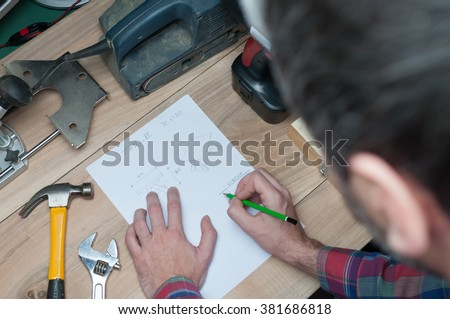 Designer with a pen and piece of paper working on a project in workshop - stock photo