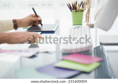 Designer working at desk using digitizer in his office - stock photo