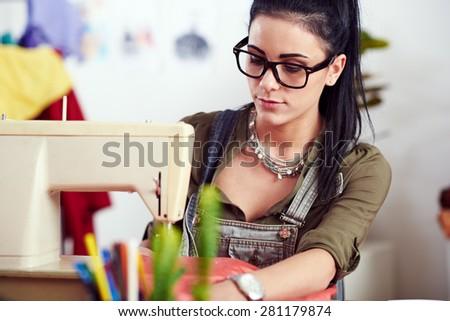 Designer working on sewing machine - stock photo