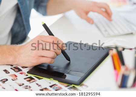 Designer working with digitizer at his desk in creative office - stock photo