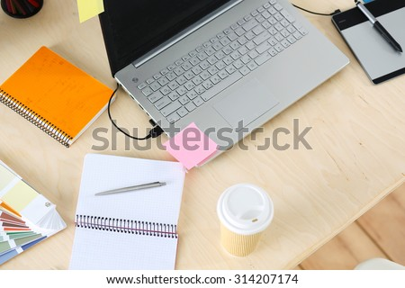 Designer workplace from top. Working table of retoucher with laptop computer and graphic tablet. Creative or advertising business concept. Empty workplace ready to be used - stock photo