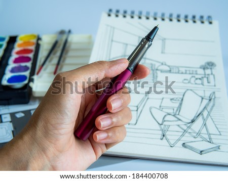 Designer works on hand drawing interior perspective &plans  of house sketch
