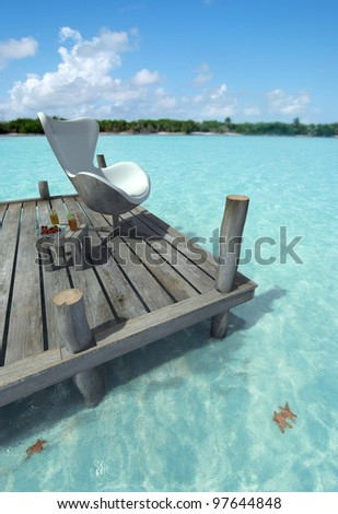 Designers chair on a peer, side table with refreshments and a beautiful Caribbean ocean