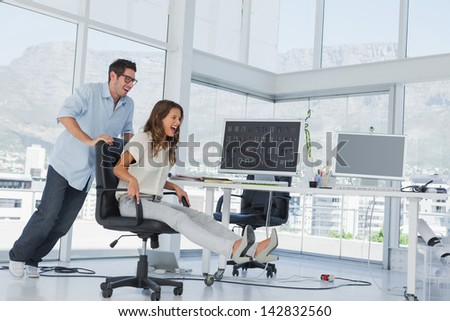 Designers having fun with a swivel chair in their office - stock photo
