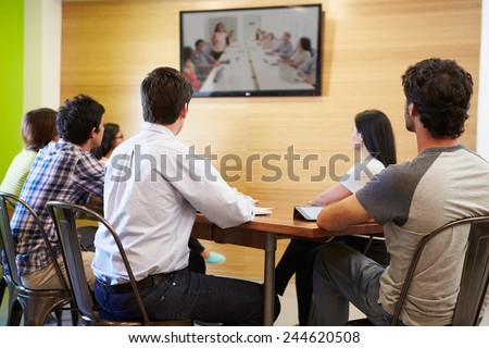Designers Sitting Around Table In Meeting Looking At Screen - stock photo