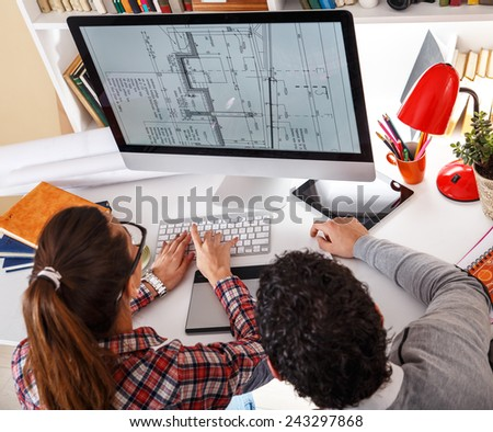 Designers working on new project.They looking in blueprint on screen and discussing.  - stock photo