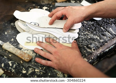 Designing shoes, occupation shoemaker.Shoemaker sews shoes - stock photo