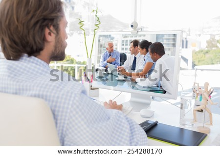 Desinger working on his computer against group of business people brainstorming together - stock photo