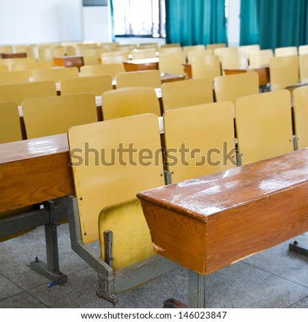 desk and chairs in classroom.
