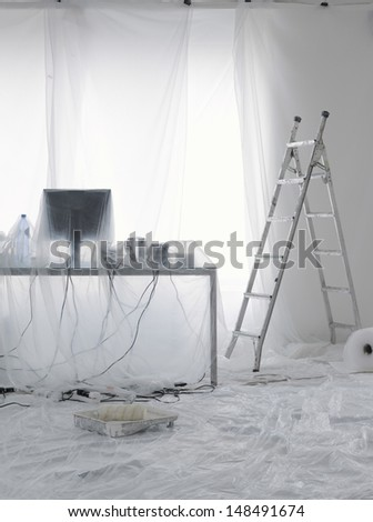 Desk and computer covered in transparent dust sheets in preparation for decoration - stock photo