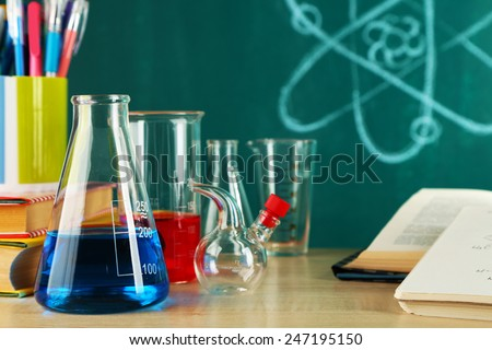 Desk in chemistry class with test tubes on green blackboard background - stock photo