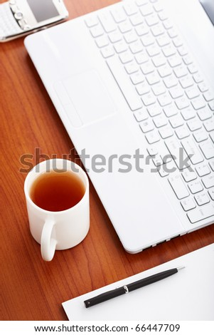 Desk in office, selective focus on nearest part of cup