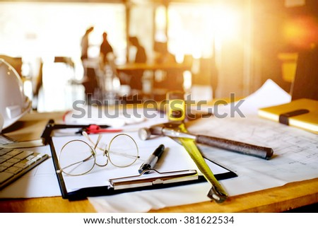desk of Architectural project in construction site or office  with mining light. - stock photo