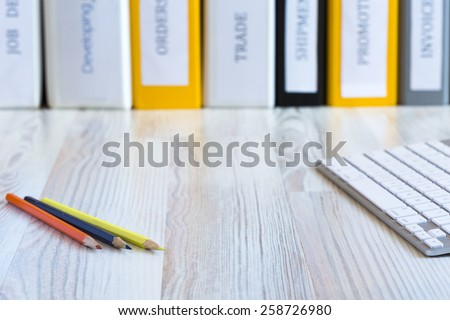 Desk of creative person. Side view on light wooded desk with color pencils and keyboard, with stack of folders on the background - stock photo