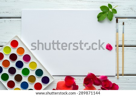 Desk of creative worker. Paints, brush, paper, rose petals and leaves. Top view background. - stock photo