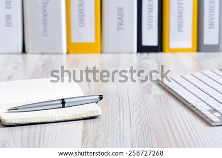 Desk of decision maker. Side view on light wooded desk with pen, stylish leaver note pad and keyboard, with stack of folders on the background - stock photo