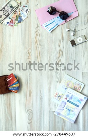 Desk of mature voyager. Travel background with essential tourist items on wooden desk passport international with entry stamps and visas exotic currency credit card  sunglasses from above