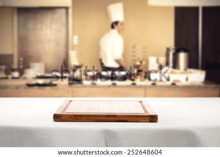 desk of wood with white tablecloth  and cook in restaurant  - stock photo