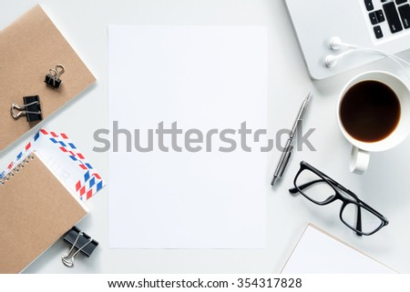 Desk with laptop, a cup of coffee and supplies, top view. The blank paper can be used to put some text or images. - stock photo