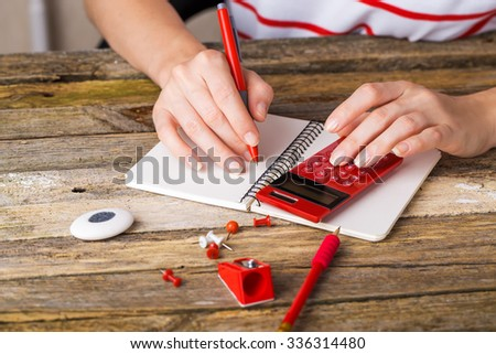 Desk with school supplies. Action hands during a lesson - stock photo