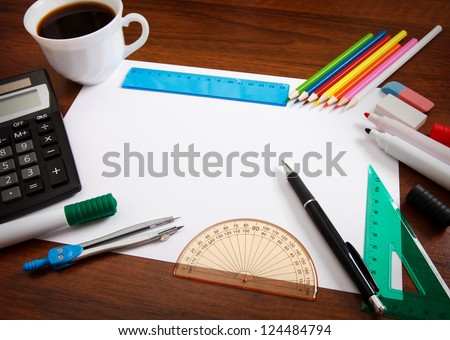 Desk with sheet of paper and stationery objects seen from above - stock photo