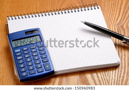 Desk with sheet of paper, calculator and stationery objects seen from above