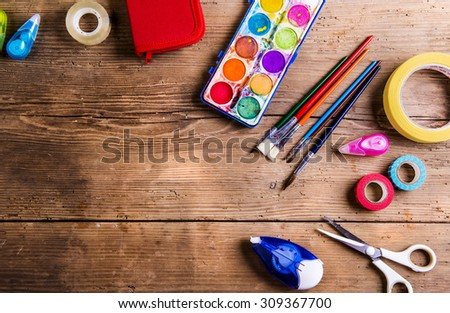 Desk with stationary and with Back to school sign. Studio shot on wooden background. - stock photo