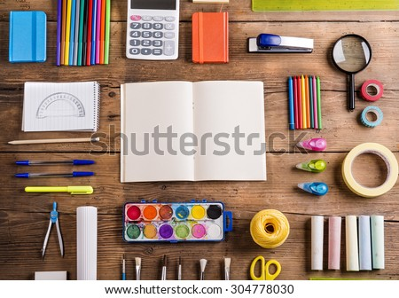 Desk with stationary and with blank notebook. Studio shot on wooden background.  - stock photo