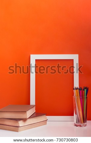 desk with white blank picture frame mock up. Pencils and books on orange background. Concept of teacher's day. Copy space