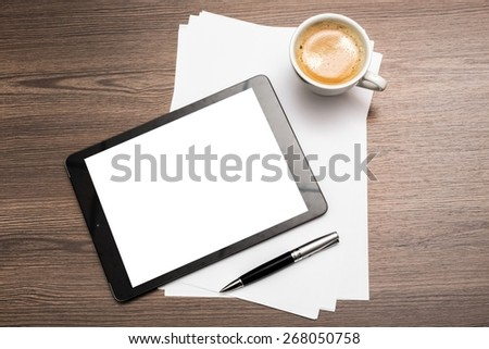 Desk. Workplace with blank digital tablet, paper, pen and cup of coffee on work table. Above view shot. - stock photo