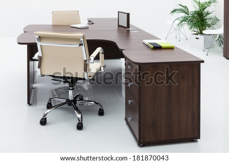 desks and leather chairs on a white wall