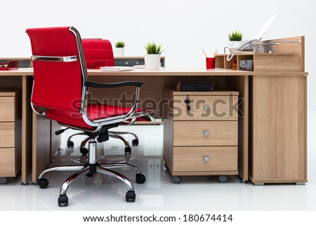 desks and red armchairs on a white wall - stock photo