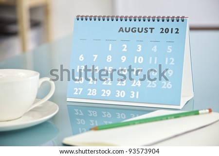 Desktop calendar sitting on a glass desk showing the month of August 2012 - stock photo
