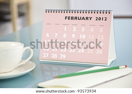 Desktop calendar sitting on a glass desk showing the month of February 2012 - stock photo