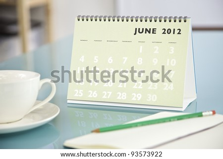 Desktop calendar sitting on a glass desk showing the month of June 2012 - stock photo