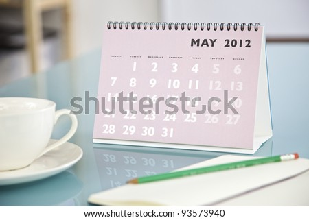 Desktop calendar sitting on a glass desk showing the month of May 2012 - stock photo