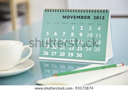 Desktop calendar sitting on a glass desk showing the month of November 2012 - stock photo